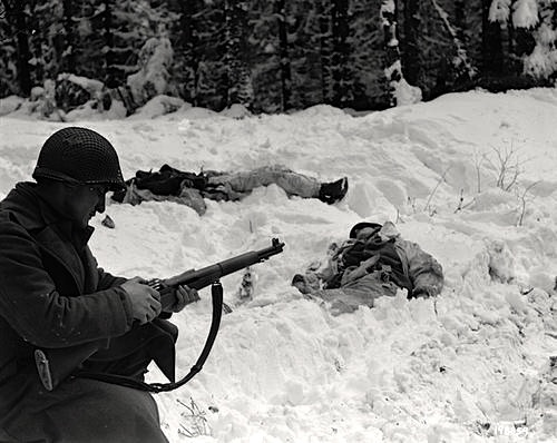 Pfc. Frank Vukasin, 333st Infantry Regiment, 83rd Division reloads his M1 near Houffalize, Belgium January 15, 1945. The 20 degree below zero temperatures often froze their guns and the men urinated on them in order to melt the ice.