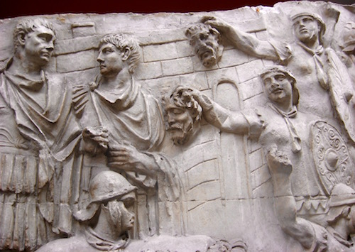 Roman soldiers showing Emperor Trajan the heads of important dead enemies during the Dacian War in c. 102 AD on Trajan's Column in Rome.
